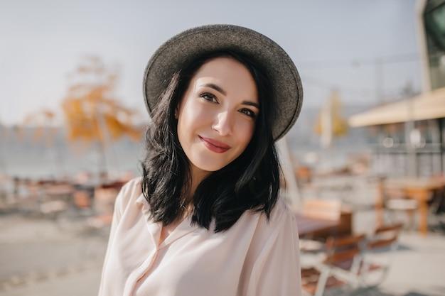 ぼかしでポーズをとる流行の灰色の帽子の熱狂的な若い女性 無料写真