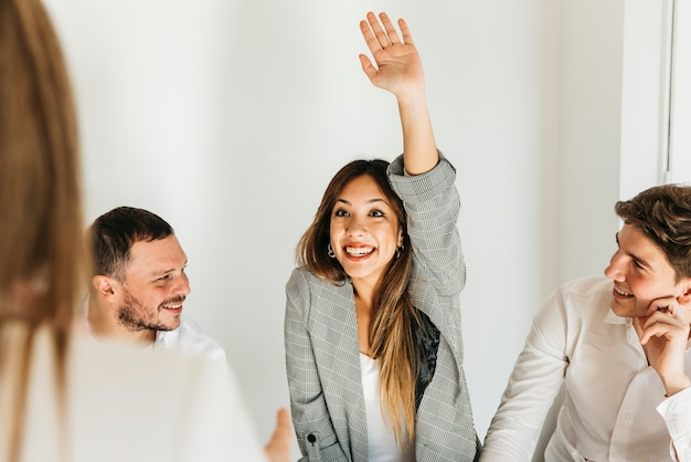 Enthusiastic young woman with raised hand Free Photo