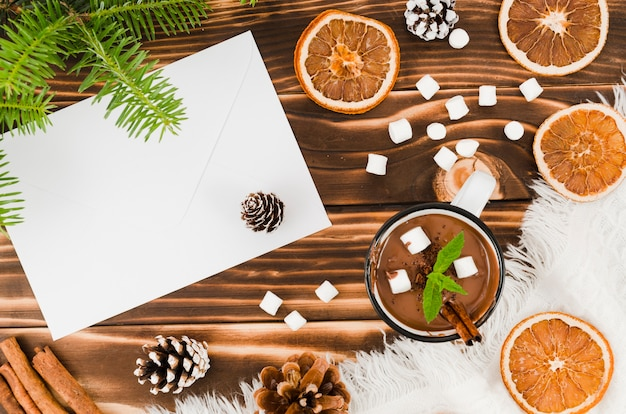 Envelope near hot chocolate, oranges and marshmallow Free Photo