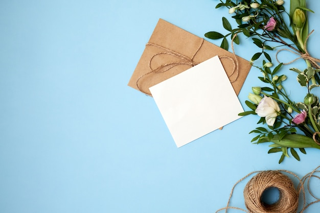 Envelope, paper card and flowers on blue background. Premium Photo