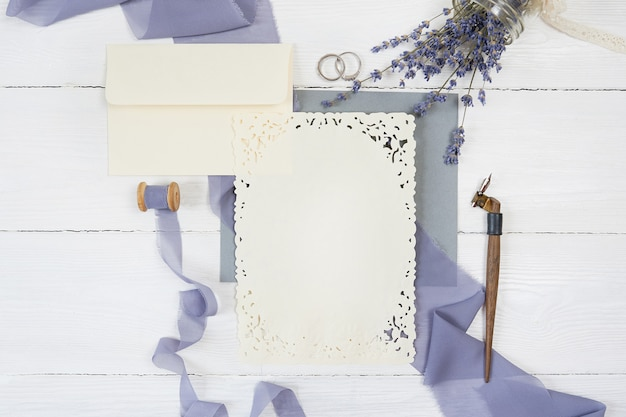 Envelope and ribbon with two wedding rings with lavender flowers and calligraphic pen Premium Photo