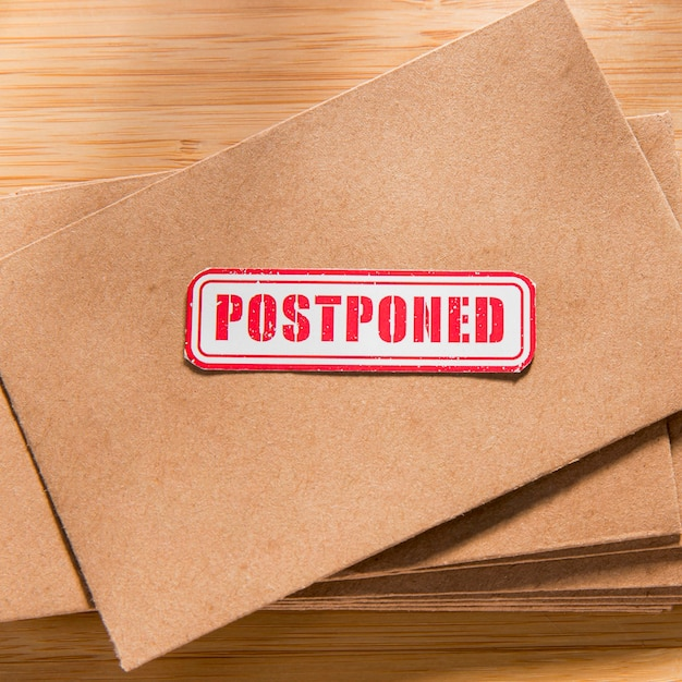 Envelope with postponed message on desk Free Photo