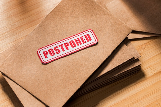 Envelope with postponed message on table Premium Photo