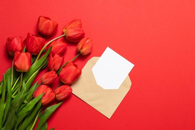 テキスト用のスペースと赤の背景に美しい赤いチューリップの封筒。閉じる Premium写真