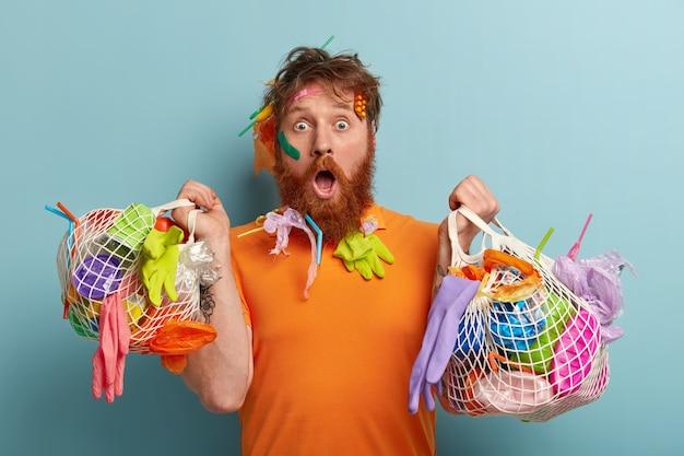 Concetto di protezione dell'ambiente. perplesso, scioccato, l'uomo barbuto dai capelli rossi fissa, stupito dal disastro della natura, raccoglie i rifiuti di plastica, modelli oltre il muro blu con due sacchi di immondizia Foto Gratuite