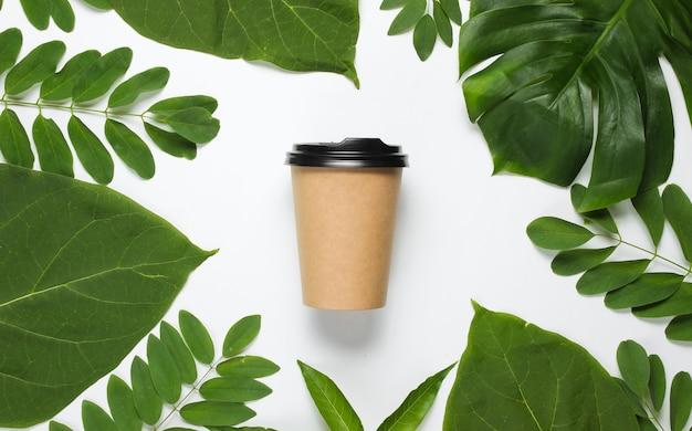 Экологически чистый натюрморт. одноразовая картонная кофейная чашка на белом фоне с зелеными тропическими листьями. Premium Фотографии