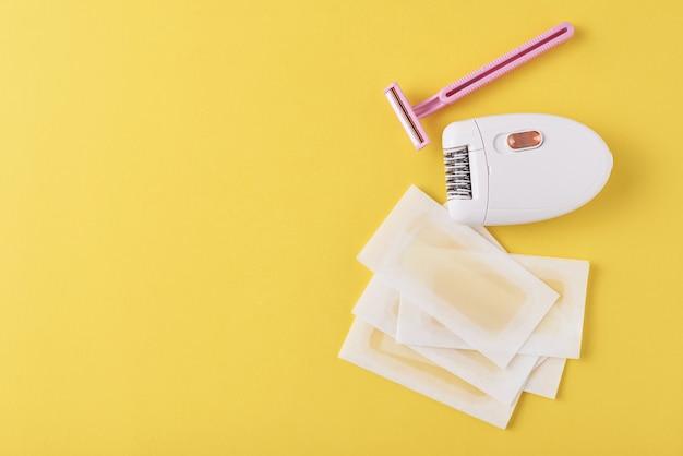 Epilator, razor and wax strips on yellow surface Premium Photo