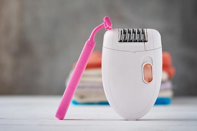 Epilator, shaving razor and bathroom towel Premium Photo