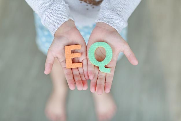 Eq (emotional quotient) sponge text on child hands. Premium Photo