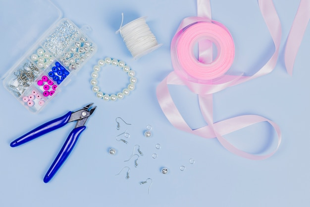 Equipment for making the hand made earrings with pink ribbon on blue background Free Photo