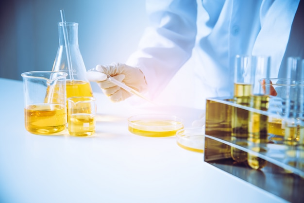 Equipment and science experiments oil pouring scientist with test tube yellow making research in laboratory. Premium Photo