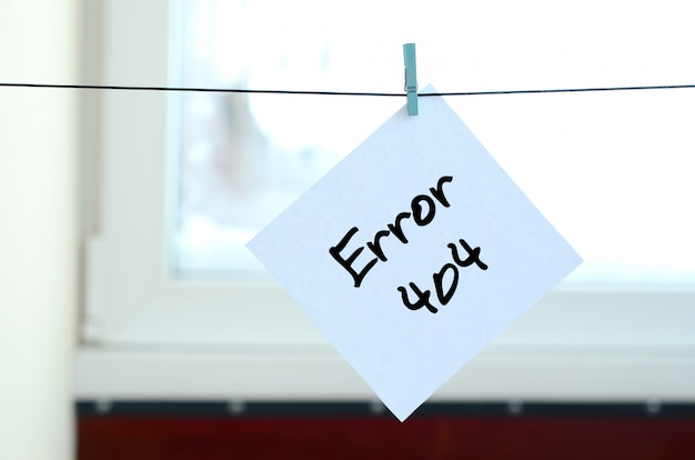 Error 404. note is written on a white sticker that hangs with a clothespin on a rope Premium Photo