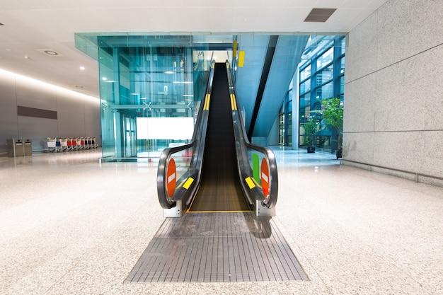Escalator of modern office building, blue toned images. Premium Photo