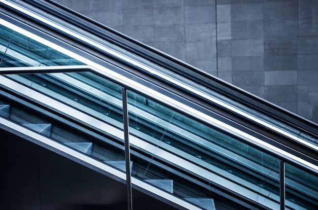 Escalators in a building with grey walls Free Photo