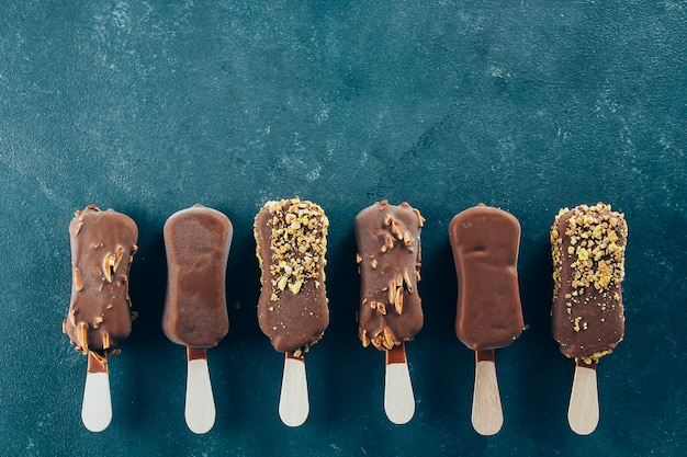 Eskimo ice cream in chocolate glaze on blue background. yummy sweet food snack treat. Premium Photo