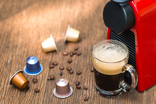 Espresso coffee machine with capsules making coffee in a glass cup. Premium Photo