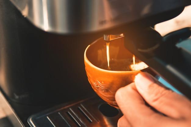 Espresso pouring from coffee machine Premium Photo