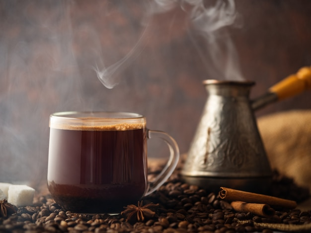 Espresso transparent glass cup and coffee beans on the table Premium Photo