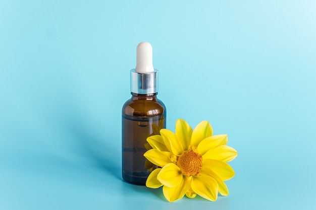 Essential oil in brown dropper bottle and yellow flower. concept natural organic beauty cosmetics product Premium Photo