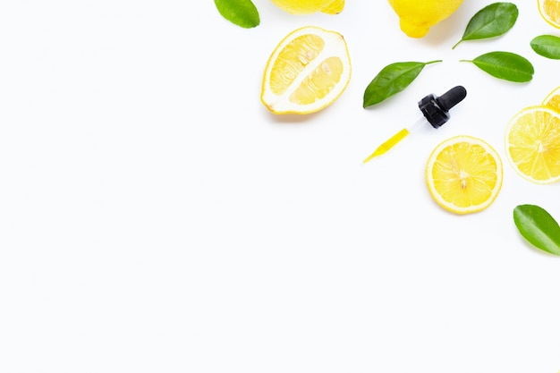 Essential oil with fresh lemon and green leaves on white Premium Photo