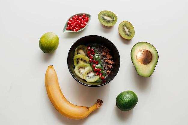 Основы приготовления миски для смузи. тарелка blake с киви, бананом, зернами граната, лаймом, мюсли и семенами чиа. здоровый завтрак. круглая композиция. Бесплатные Фотографии