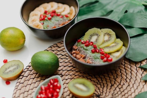 Основы приготовления миски для смузи. тарелка blake с киви, бананом, зернами граната, лаймом, мюсли и семенами чиа. здоровый завтрак. тропическое настроение. Бесплатные Фотографии
