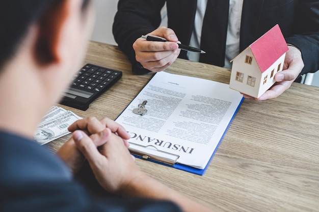 Estate agent broker reach contract form and presentation to client signing agreement contract real estate with approved mortgage application form, buying mortgage loan offer for and house insurance Premium Photo