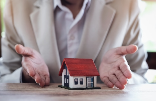 Estate agent gives model house to agreement with customer to sign contract for insurance Premium Photo