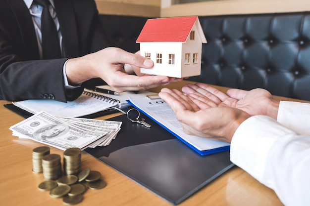 Estate agent sending house model to client after signing agreement contract real estate with approved mortgage application form, concerning mortgage loan offer for and house insurance Premium Photo