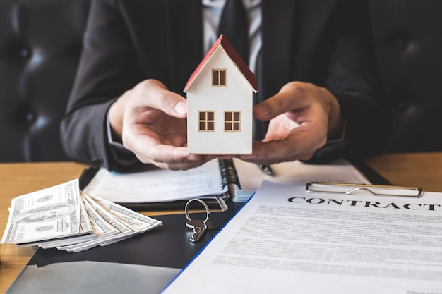 Estate agent sending house model to client after signing agreement contract real estate with form Premium Photo