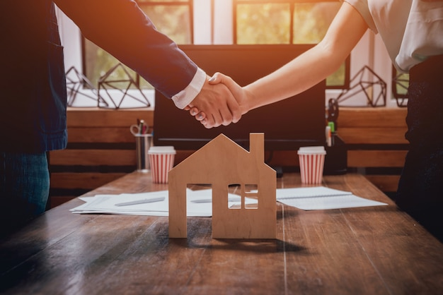 two people holding hands above a house form in wood