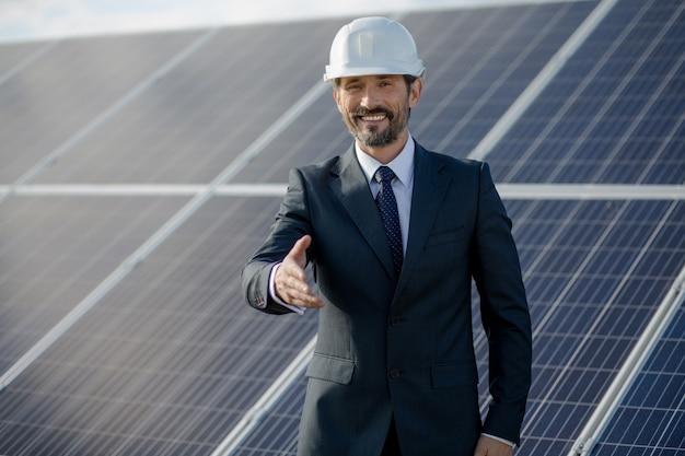 Бизнесмен на солнечной энергии etation, держа руку. Premium Фотографии