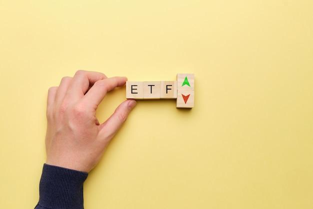 黄色の背景に上下の矢印の付いたetfコンセプト。 Premium写真