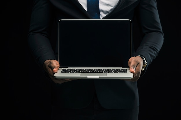 Ethnic businessman showing laptop Free Photo