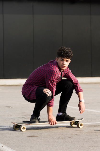 Ethnic hipster in checkered shirt riding skateboard squatting Free Photo