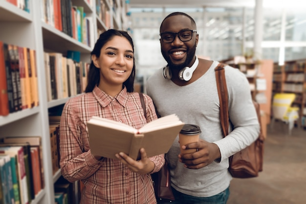 Ethnic indian mixed race girl and black guy in library | Premium Photo