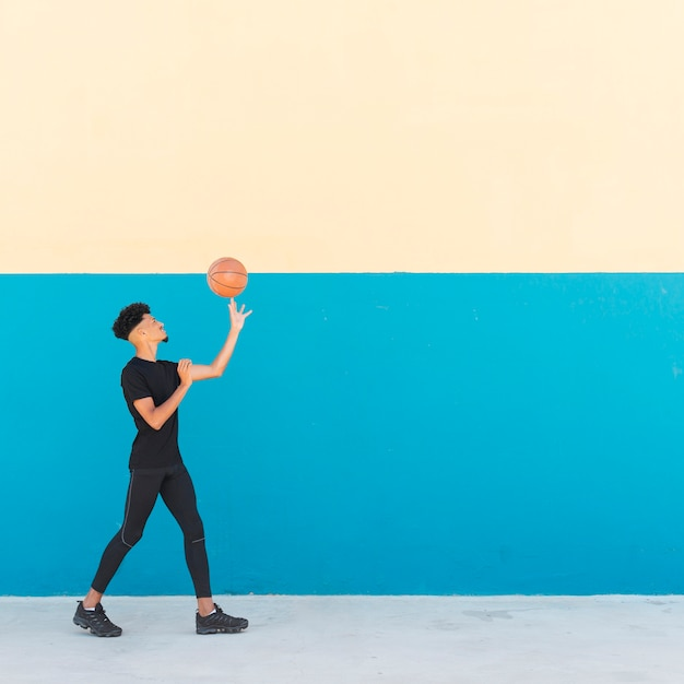 Ethnic male spinning basketball on finger Free Photo