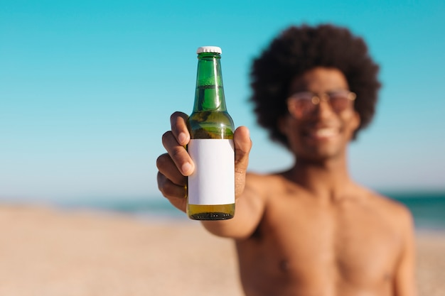 Ethnic man holding bottle of beer Free Photo
