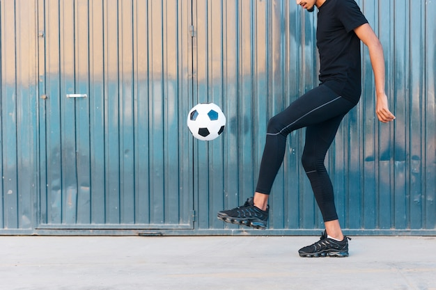 Ethnic man playing football on street Free Photo