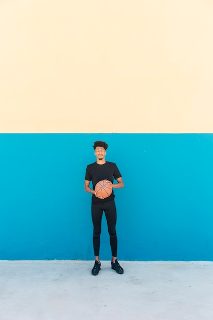 Ethnic player with basketball on street Free Photo