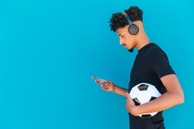 Ethnic player with football using phone and headphones Free Photo