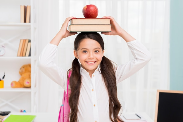 Ethnic schoolgirl holding books on head Free Photo