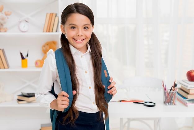 Ethnic schoolgirl holding straps of knapsack Free Photo
