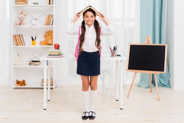 Ethnic schoolgirl standing under book roof Free Photo