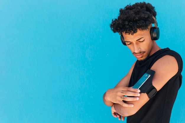 Ethnic sportsman with headphones using phone in armband Free Photo