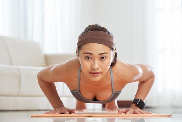 Ethnic sportswoman training on mat Free Photo