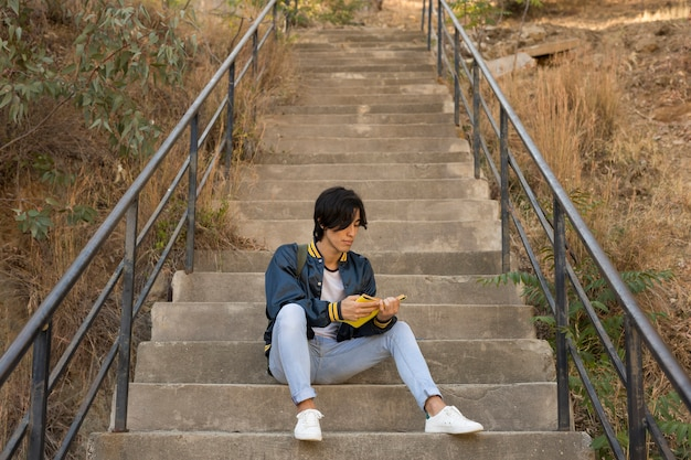 Ethnic teenager sitting with book on stairs Free Photo