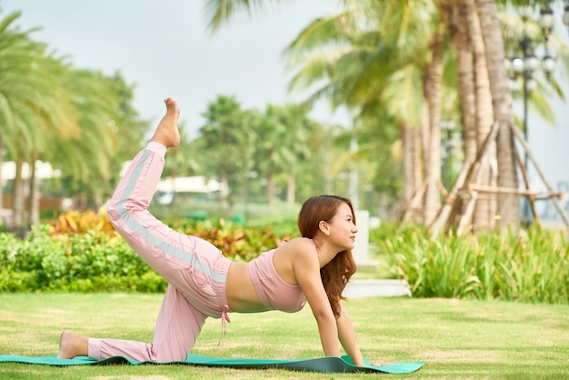 Ethnic woman doing yoga in park Free Photo