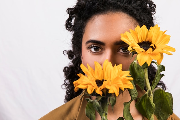 Ethnic woman with yellow flowers near face Free Photo