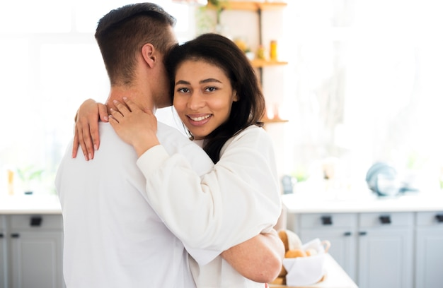 Ethnic young female hugging boyfriend and looking at camera Free Photo